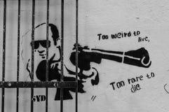 Street art on a wall with man pointing a gun. Soho, London, UK, June 8 2014: Graffiti on a wall behing an iron gate. with man pointing a gun and the words Too Stock Photos