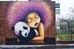 Street art wall painting of a girl with a panda in Paris Stock Photos