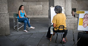 Street artist. Santiago de Compostela, Spain - August 15, 2011 - Street artist making a caricature of a beautiful woman in the streets of Santiago de Compostela Stock Image