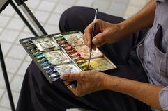 Street artist. An Asian Chinese artist painting on street Stock Photography