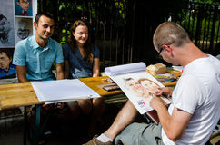 Street artist in Bucharest. Street artist sketching a young couple in Bucharest, Romania, 2015. Street delivery Royalty Free Stock Photo