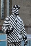 Street artist standing still along the Southbank,London,UK. A street artist covered in black and white stripes stands still Royalty Free Stock Images