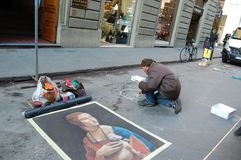 Street artist draws on the asphalt portrait of a lady with an ermine. Florence, Christmas in Italy. Tourism, holidays, attractions, lifelong experiences royalty free stock image