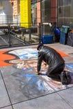 Street artist draws on asphalt Uncle Sam in Paris Stock Photo