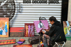 Street artist draws and sells paintings in Belgium. The man in Belgium paints a picture on the street and sell their works. Artist in work clothes, with paints stock photo