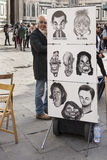 Street artist expects walking around tourists Stock Image