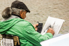 Street artist in the Grand Place, Brussels. A street painter works to the tourists, inspired by cellphone pictures, in the center of Grand Place, in Brussels stock photos