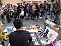 Street artist in Rome. Street artist and his drawings in the Rome center royalty free stock image