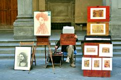 Street artist in Italy. Painter selling art on the streets of Florence, Italy. artisan , craftsman concept living from his work Royalty Free Stock Photo
