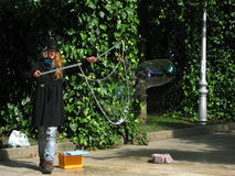 A street artist with a little cat doing soap bubbles Stock Image