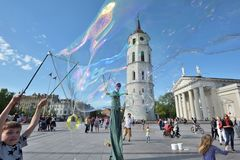 Street artist makes big soap bubbles. Vilnius, Lithuania, May 4: Unknown street artist makes big soap bubbles in a public square on May 4, 2018 in Vilnius Stock Photography