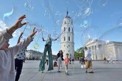 Street artist makes big soap bubbles. Vilnius, Lithuania, May 4: Unknown street artist makes big soap bubbles in a public square on May 4, 2018 in Vilnius Stock Photos