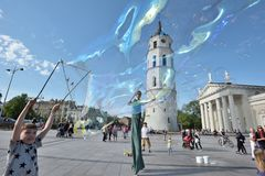 Street artist makes big soap bubbles. Vilnius, Lithuania, May 4: Unknown street artist makes big soap bubbles in a public square on May 4, 2018 in Vilnius Royalty Free Stock Image