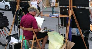 Street artist makes and sells watercolours. Florence, Italy - August 31, 2019: back view of street artist makes and sells watercolours on the Piazza Della stock footage