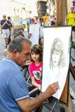 Street artist is making a portrait sketch of a young tourist stock image