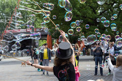 Street artist making soap bubbles on the street. Berlin, Germany - may 13, 2016: Street artist making soap bubbles on the street in Berlin, Germany royalty free stock photo