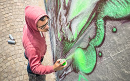 Street artist painting colorful graffiti on generic wall. Modern art concept with urban guy performing and preparing live murales with green aerosol color Royalty Free Stock Images