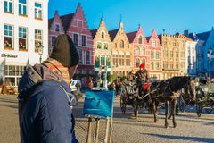 Street artist paints a Horse carriage of Brugge Stock Image