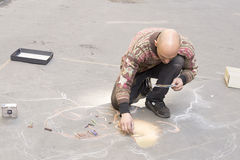 Street artist paints a picture on the pavement Stock Images