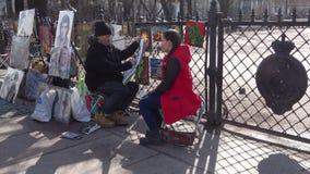 Street artist paints a portrait of a young girl. Nevsky prospect, Saint Petersburg. SAINT PETERSBURG, RUSSIA - APRIL 09, 2018: Street artist paints a portrait of stock footage