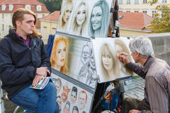 Street artist paints a portrait of young man and girl in Prague Stock Photo