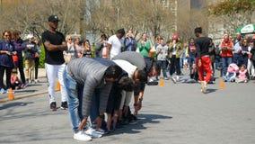 Street Artist performs long jump over row of people. New York City, USA - April 2018: Street Artist performs long jump over row of people stock footage