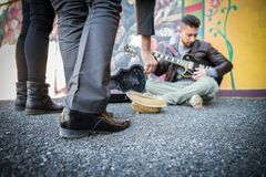 Street artist playing guitar on the streets. Street artist peforming om the streets - People listening man playing guitar and giving charity Stock Images