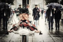 Street artist playing violin. On a rainy day bringing the  boring city to life Royalty Free Stock Image