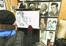 Street artist portraitist. caricatures of people. Who visit the San Geminiano fair on the day of the patron saint of Modena royalty free stock image