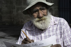 Street artist poses in Havana, Cuba. HAVANA, CUBA - DECEMBER 13, 2016 - An elderly artist poses while demonstrating some of his work on the streets of Havana Stock Images