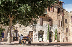 Street artist in San Gimignano. Local painter selling his art under a tree in San Gimignano, Tuscany, Italy Stock Image