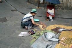 Street artist in Siena. Siena, Italy - July 27, 2015: Street artist drawing on the floor stock photos