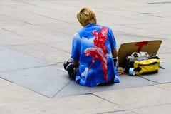 Street artist sitting on the ground in Alexanderplatz stock photography