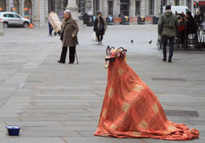 Street artist in the strange costume is entertaining passers Royalty Free Stock Image