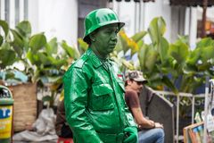 Street artist transformed into a green statue of a soldier. Jakarta, Jawa, Indonesia - Juli 2018 royalty free stock photo