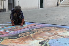 Street artist in Venice. Venice, Italy-May 6th 2015. Street artist drawing picture in a square of Venice stock photography