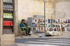 The street artist will sell their own work on street Lisbon (Portugal). He helps his friends - two dogs. November, 2013 Stock Photos