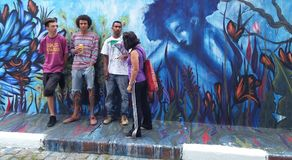 Street artists gathered around their blue mural about a woman and nature stock images