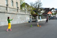 Zug, ZG / Switzerland - 20 April, 2019: street artists making giant soap bubbles during Easter weekend celebrations on Lake Zug royalty free stock image