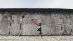 Street artwork of a little girl trying to grab the red heart-shaped balloon