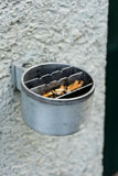 Metal ashtray on a wall full with cigarette old retro style not cleaned Royalty Free Stock Image