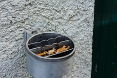 Metal ashtray on a wall full with cigarette old retro style not cleaned Royalty Free Stock Images