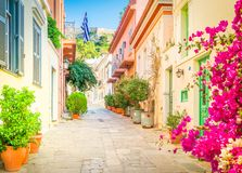 Street of Athens, Greece. Small paved street of Placa district with Acropolis hill in Athens, Greece with flowers, toned royalty free stock photos