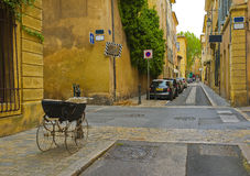 Street with Baby Carriage, Aix-en-Provence, France. A charming street with mustard gold colored buildings and a baby buggy in the foreground in historic AIx en Royalty Free Stock Photos