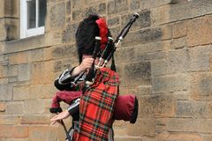 The street bagpiper in the city Edinburgh in Scotland. The street bagpiper is busy with his bagpipe in one of the streets, Royal Mile in the city Edinburgh in Royalty Free Stock Photography