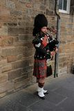 The street bagpiper in the city Edinburgh in Scotland. The bagpiper is playing in one of the streets, Royal Mile in the city Edinburgh in Scotland in the summer Stock Image