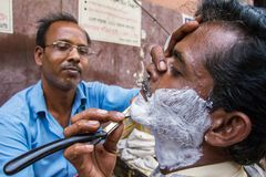 Street barber shaving a man Stock Images