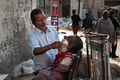 Street barber shaving a man on the street in Amritsar. India Stock Photos
