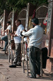 Street barbers shaving men on the street in market. Agra. India Royalty Free Stock Photo