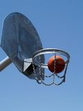 Street baskeball. Basketball going into the hoop Stock Photos
